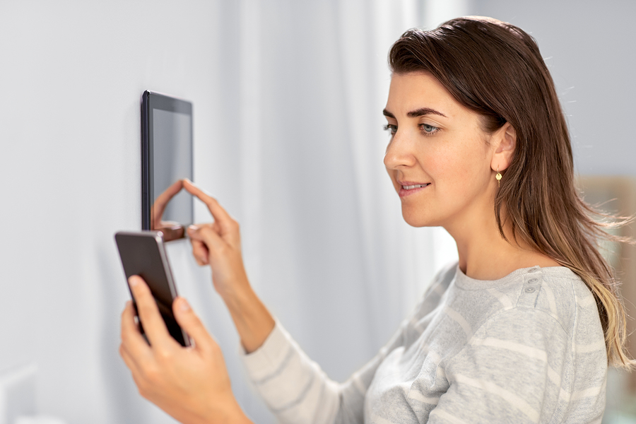 automation, internet of things and technology concept - woman using tablet pc computer and smartphone at smart home